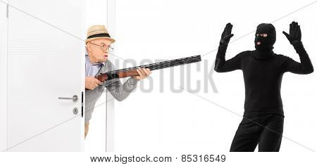 Senior with rifle catching a burglar isolated on white background