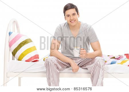 Guy drinking a coffee seated on a bed isolated on white background