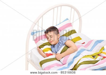 Cute little boy sleeping in a comfortable bed isolated on white background