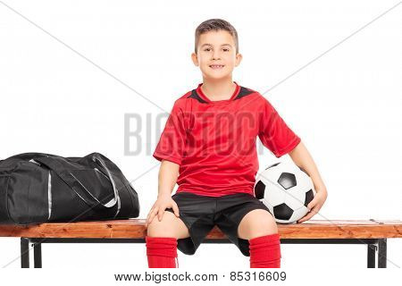 Little boy holding a soccer ball seated on a bench isolated on white background