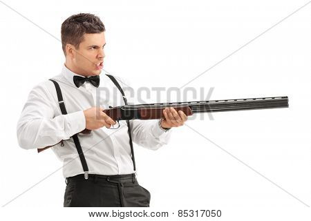 Angry young man shooting with a shotgun isolated on white background