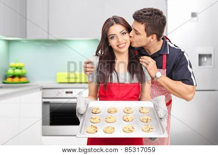 Young couple baking cookies in the kitchen at home