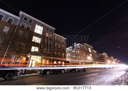 Cars drive by apartment building complex at night