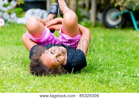 African girl playing on meadow in front of picket fence rolling around