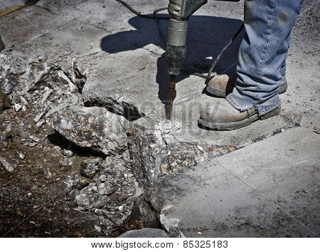 Man drilling cement concrete road