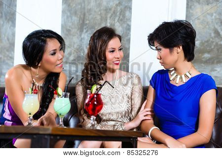 Asian young and handsome group of party people or girls night out drinking cocktails in fancy night club