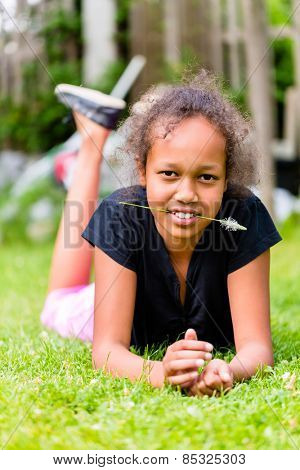 Black girl lying with grass blade on meadow