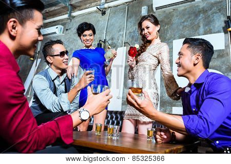 Asian young and handsome group of party people or friends drinking cocktails and shots in fancy night club