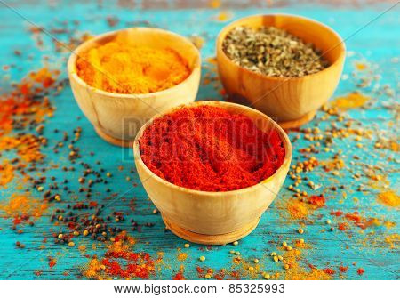 Different seasoning in wooden bowls on color wooden table background