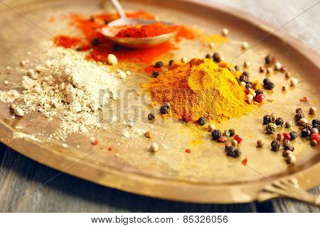 Various of spices on metal tray and rustic wooden table background