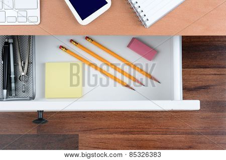 High angle shot of an open desk drawer showing the items inside. The top of the desk has a computer keyboard Cell Phone and note pad. The neat drawer has pencils paper and organizer.
