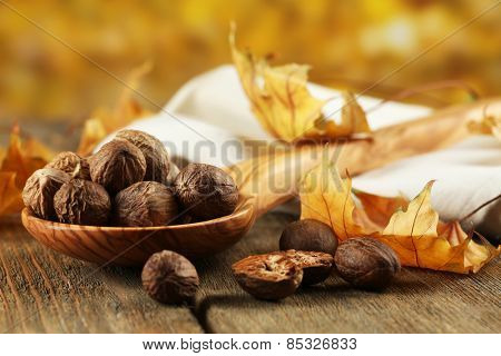 Nutmeg in wooden spoon on table on bright background