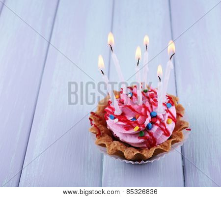 Birthday cup cake with candles and sparkles on color wooden background