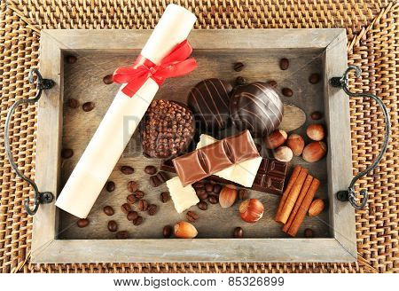 Sweets with rolled paper on wooden stand and wicker mat background