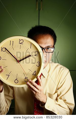 Man holding a clock to his face