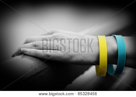 Hand with blue-yellow bracelet - colors of flag of Ukraine