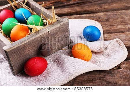 Easter eggs in box on vintage wooden planks background