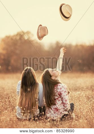Young girls having fun outside, throwing hats up and smile