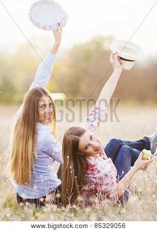 Young girls having fun outside, hats up and smile