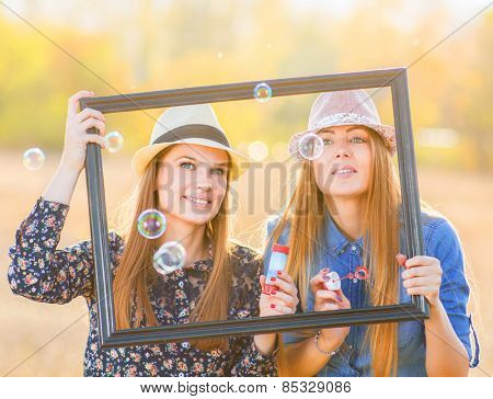 Two friends with picture frame outside playing and enjoying