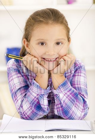 Little girl doing homework, looking at camera and smile