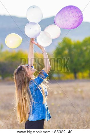 Girl playing with bunch of balloons in nature
