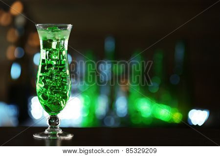 Green cocktail on table on dark background