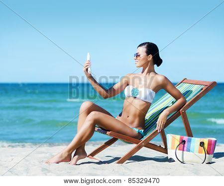 Young, beautiful and sexy woman with a sun protection cream on a summer beach