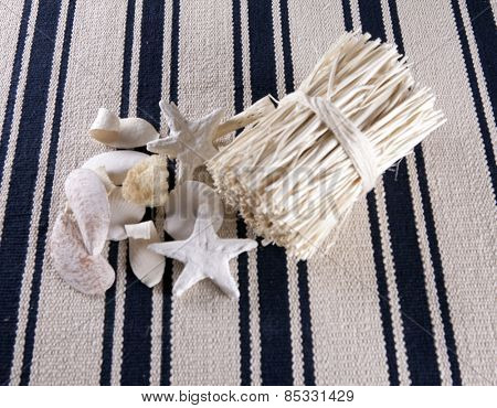 Beautiful collage of starfish, shells, bundles of straw on the old retro striped rug.