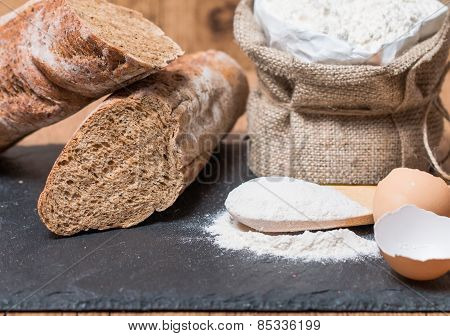 Bread Roll Or French Baguette And Flour On Black