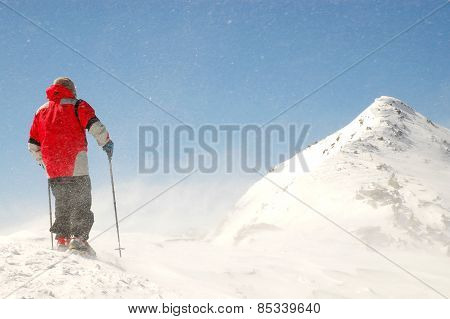 Climber Facing Wind And Snow On Mountain Summit