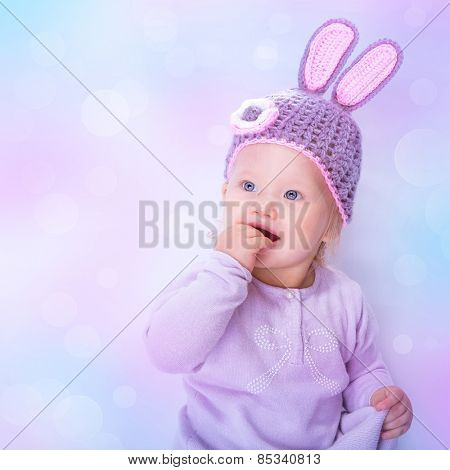 Portrait of a cute Easter bunny baby girl over blur pink blue bokeh background, sweet little child wearing purple hat with rabbit ears, celebrating religious holiday