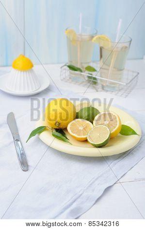 Plate with fresh lime and lemon and two glass of lemonade