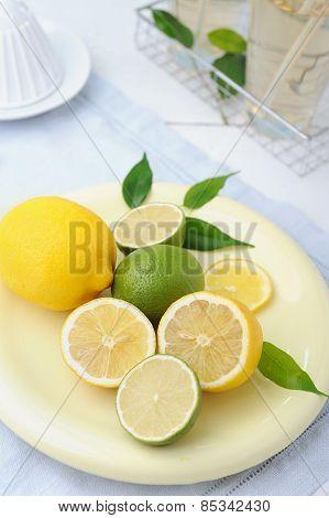 Bowl with fresh lime and lemon and two glass of lemonade