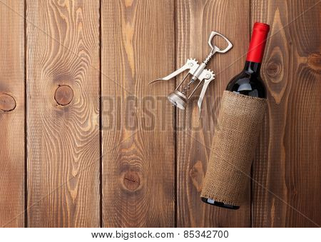 Red wine bottle and corkscrew on wooden table background. Top view with copy space