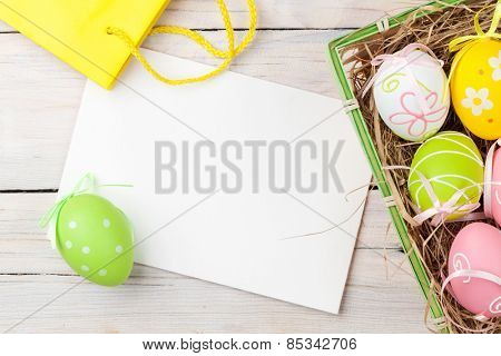 Easter background with colorful eggs, yellow tulips and greeting card over white wood. Top view with copy space