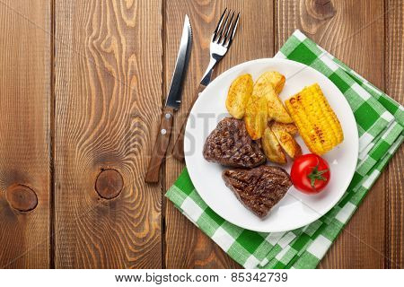 Steak with grilled potato, corn, salad and tomato over wooden table. Top view with copy space