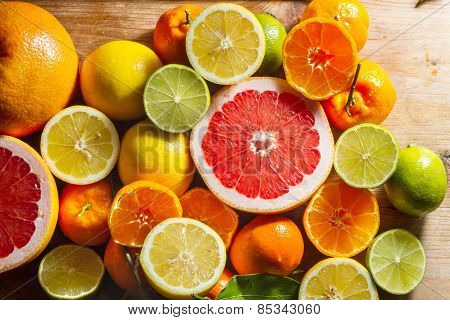 Pink Grapefruit And Other Citrus Fruit Against Wooden Background.