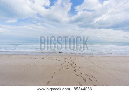 Footprints on the beach sand. Wide angle with sea and clouds