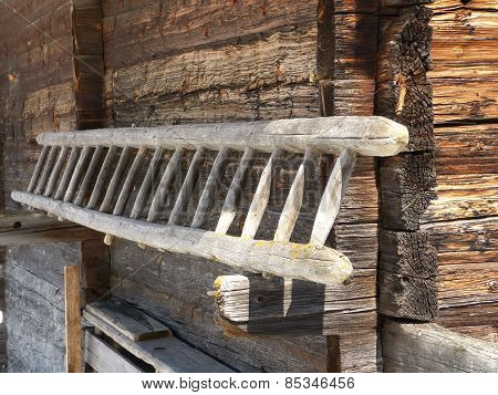 a wooden ladder on the wall of the old cowshed