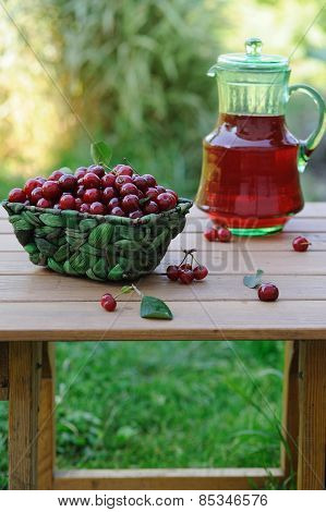 Jug Of Juice And Basket With Ripe Cherries On Wooden Table Outdoor