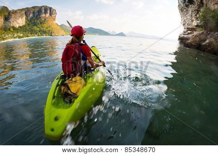 Young lady paddling the kayak in a bay with limestone mountains