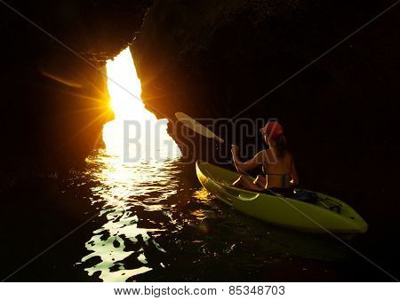 Young lady paddling the kayak from the dark cave