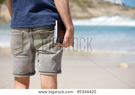 Man On Vacation Holding Diary Book At The Beach