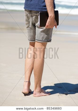 Barefoot Man Holding Agenda Book At The Beach