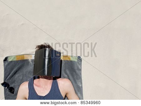 Man Lying Down On A Towel At The Beach With Book Covering Face