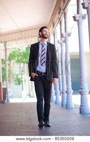 Happy Businessman Walking Outside On Sidewalk In The City