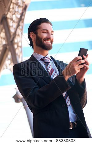 Smiling Businessman Sending Text Message On Mobile Phone