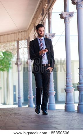 Smiling Businessman Walking On Sidewalk With Mobile Phone