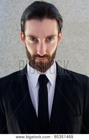 Cool Male Fashion Model With Beard Posing In Black Suit And Tie